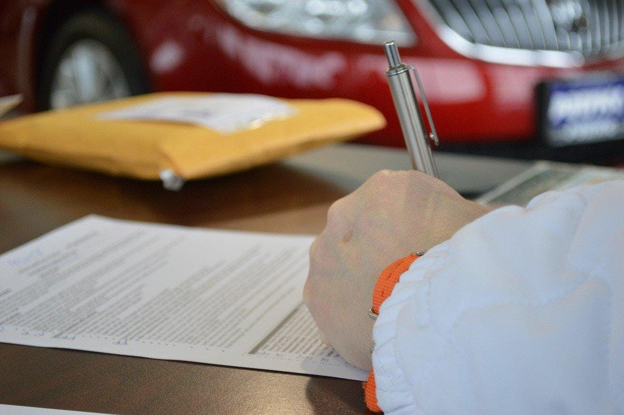 Man signing a vehicle equity release loan