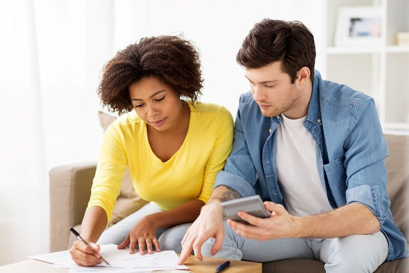 Couple budgetting to save money on expenses